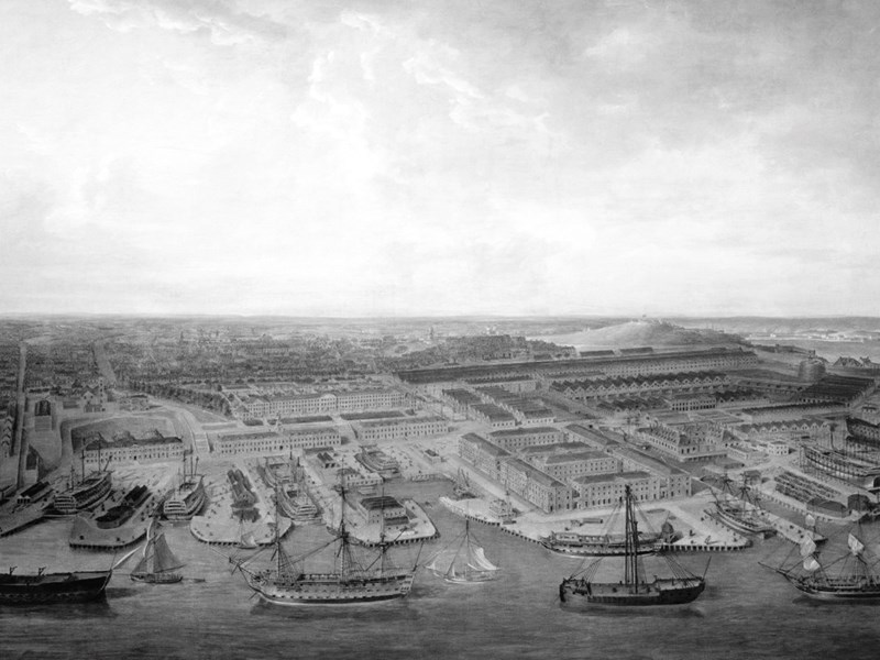 A historical maritime black and white picture of a port and numerous sailing vessels
